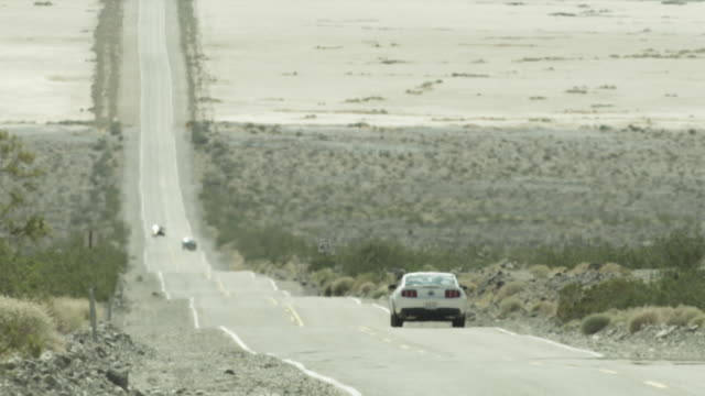 Wide shot of cars travelling along a road in Death Valley, Utah.
