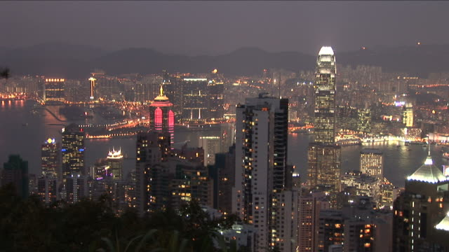 wide shot of city at night from victoria peak in hong kong china - central plaza hong kong stock-videos und b-roll-filmmaterial
