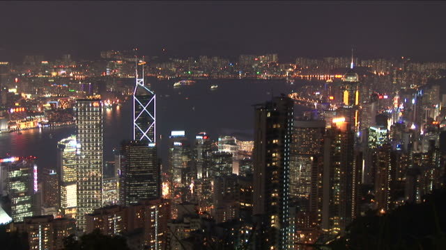 wide shot of city at night in hong kong china - bank of china tower hong kong stock videos and b-roll footage