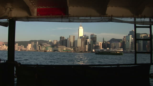 wide shot of city from a moving ferry in hong kong china - traghetto star video stock e b–roll