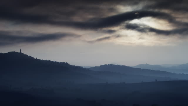 wide shot of clouds passing across moon in italian countryside / piensa, tuscany, italy - luna video stock e b–roll
