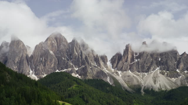 Wide shot of clouds passing over mountains range / Dolomites, Italy