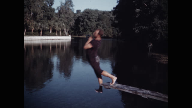 wide shot of clown diver diving into lake - misfortune点の映像素材/bロール