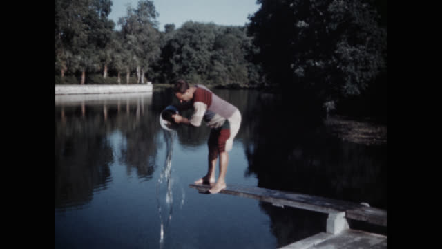 stockvideo's en b-roll-footage met wide shot of clown man pouring water into lake - emmer
