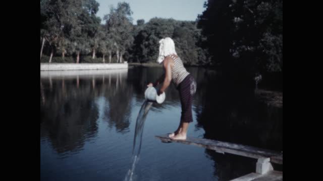 vidéos et rushes de wide shot of clown man pouring water into lake - seau