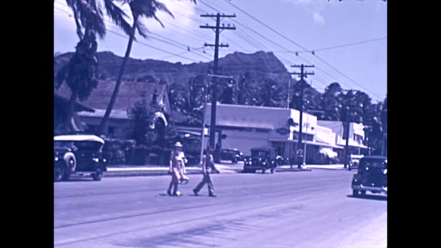 wide shot of coast and roadside / waikiki beach with royal hawaiian and moana surfrider hotels in the background /kalakaua avenue looking west... - 1940 1949 stock-videos und b-roll-filmmaterial
