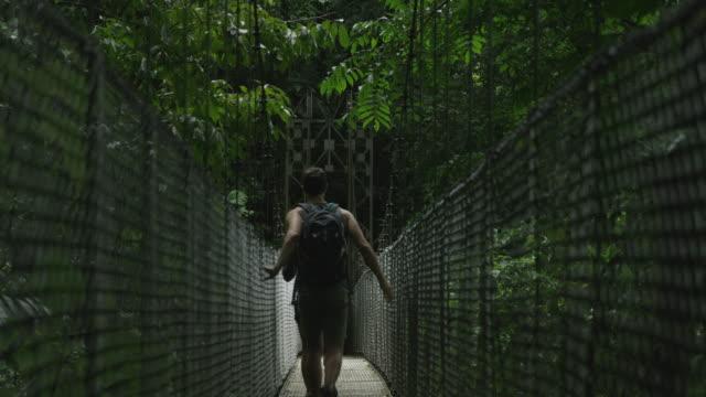 Wide shot of couple crossing hanging bridge in jungle / Arenal, Costa Rica