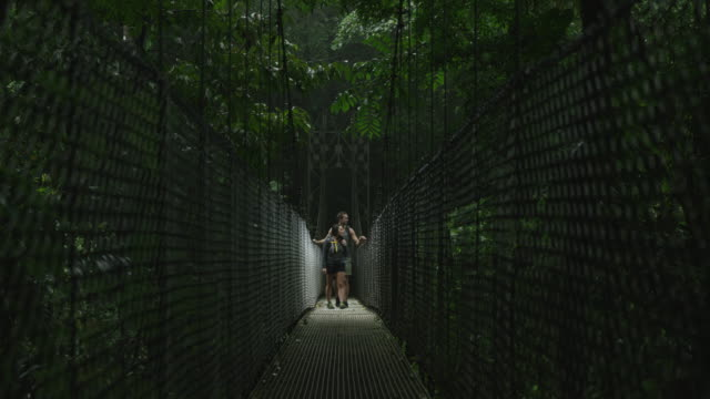 Wide shot of couple crossing hanging bridge in jungle / Arenal, Costa Rica