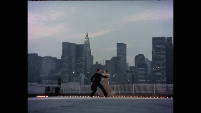 wide shot of couple dancing on pier against new york skyline at dusk, manhattan, new york city, new york state, usa - イブニングドレス点の映像素材/bロール