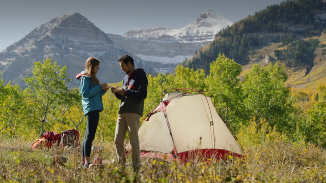 wide shot of couple kissing with food cooked on camping stove / american fork canyon, utah, united states - american fork canyon bildbanksvideor och videomaterial från bakom kulisserna