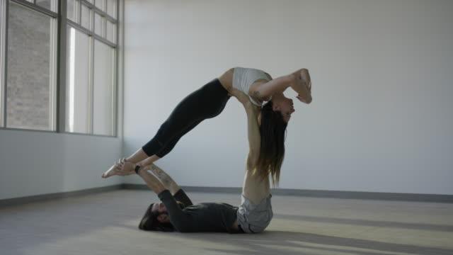 vídeos de stock, filmes e b-roll de wide shot of couple practicing acro yoga in studio / orem, utah, united states - orem utah