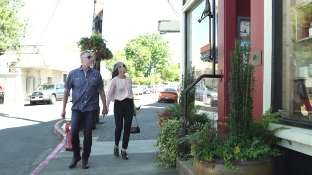 wide shot of couple walking in the city - 50 59 years stock videos & royalty-free footage