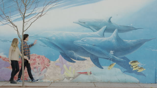 wide shot of couple walking near mural of fish and coral reef / provo, utah, united states - provo stock videos & royalty-free footage