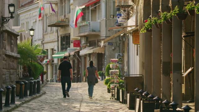 wide shot of couple walking on cobblestone street / veliko tarnovo, bulgaria - bulgaria stock videos & royalty-free footage
