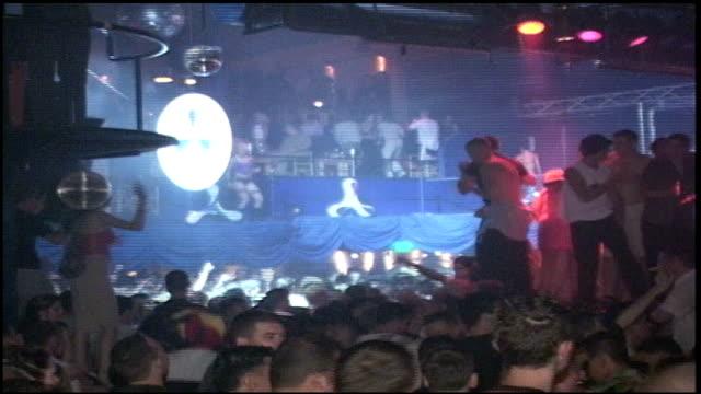 vidéos et rushes de wide shot of crowd dancing in rave nightclub - sortir en boîte de nuit