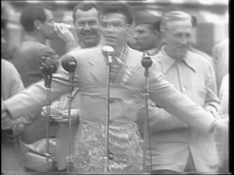 vídeos de stock e filmes b-roll de wide shot of crowd watching auction / medium shots of bob hope on stage with frank sinatra as sinatra pins takes orchids out of a box hope is holding... - frank sinatra