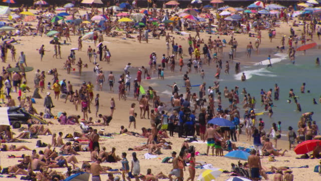 vídeos de stock, filmes e b-roll de wide shot of crowded bondi beach on a sunny summers day point of view from behind the skate park facing north bondi / zoom into crowd swimming... - barraca de sol