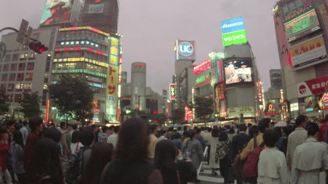 wide shot of crowds and neon signs in Ginza at dusk / Tokyo