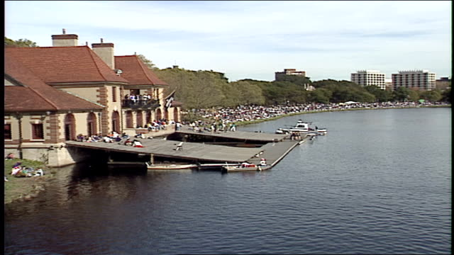 wide shot of crowds at river at rowing teams on boats in head of the charles regatta in boston - チャールズ川点の映像素材/bロール