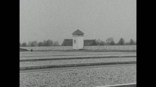 wide shot of dachau concentration camp grounds, zoom into a sentry tower; 1966. - horizon over land stock videos & royalty-free footage