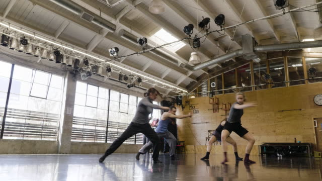 wide shot of dance troupe rehearsing in dance studio - moderner tanz stock-videos und b-roll-filmmaterial