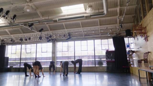Wide shot of dance troupe warming up and stretching