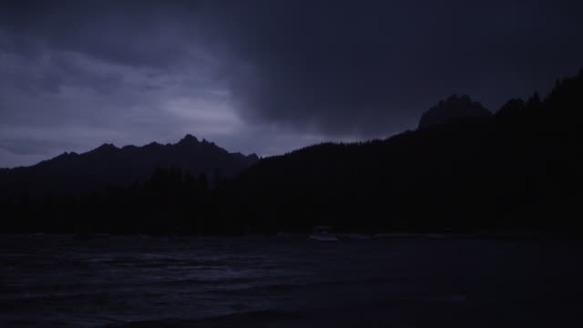 wide shot of dark clouds over silhouetted mountain and lake / redfish lake, idaho, united states - real time stock videos & royalty-free footage