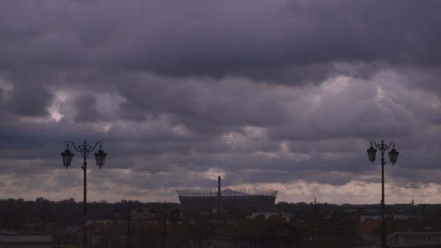 wide shot of dark, stormy clouds over the national stadium in warsaw, poland. - weather stock videos & royalty-free footage