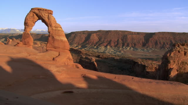 Wide shot of Delicate Arch at sunset -- no people visible - pan