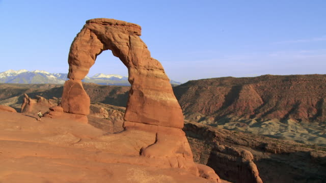 Wide shot of Delicate Arch with lone female hiker approaching the base