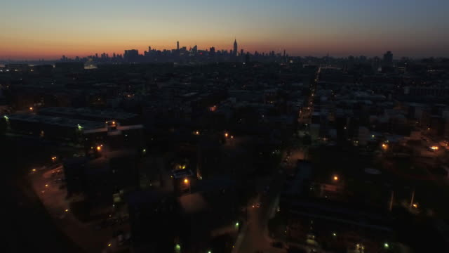 vídeos y material grabado en eventos de stock de wide shot of early morning lights in hoboken with nyc skyline lit up by sunrise in the distance - orange nueva jersey