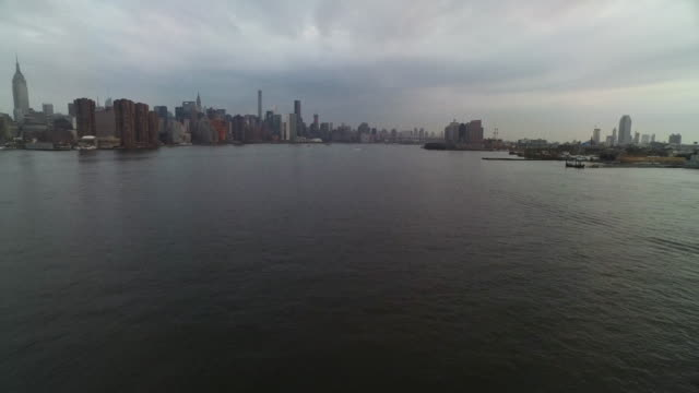 wide shot of east river with nyc skyline at left of frame - east river stock videos & royalty-free footage