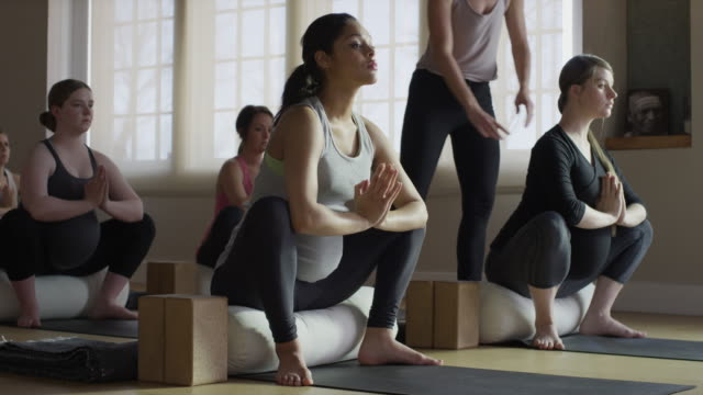 wide shot of expectant mothers and instructor in yoga class / provo, utah, united states - mature women stock videos & royalty-free footage