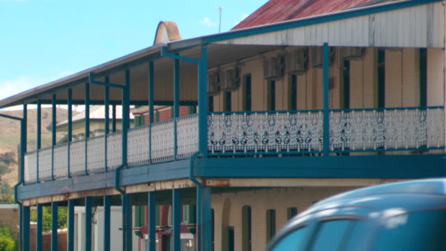 Wide shot of exterior of historic building with large second floor verandah with wrought iron ballustrade