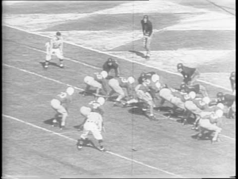 Wide shot of fans / Wide shot of Georgia Tech against Tulsa near the goal line and Quarterback Frank Broyles handoffs for a touchdown / wide shot of...