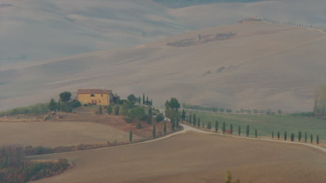 wide shot of farm house in rural countryside / piensa, tuscany, italy - masseria video stock e b–roll