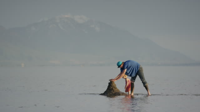 Wide shot of father and daughter scooping mud into pile at lake / Vineyard, Utah, United States