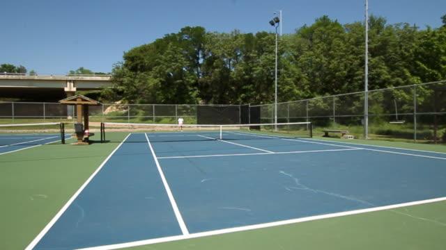 vidéos et rushes de wide shot of female tennis player on far side of cour being served in slow motion. - terrain de jeu