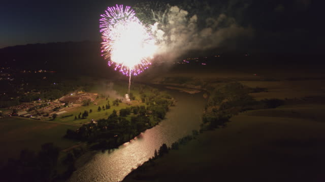 wide shot of fireworks over the river - river yellowstone stock videos & royalty-free footage