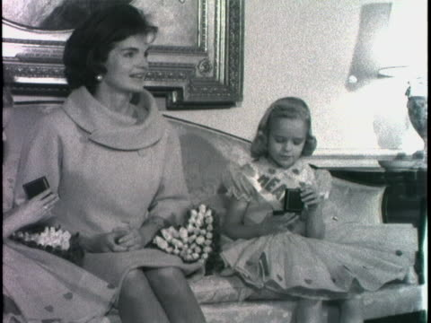 wide shot of first lady jacqueline kennedy walking into a room with two little girls. she walks with them over to a sofa. she sits in the middle with... - jackie kennedy stock videos & royalty-free footage