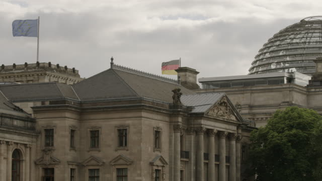 Wide shot of flags on parliament building / Berlin, Germany