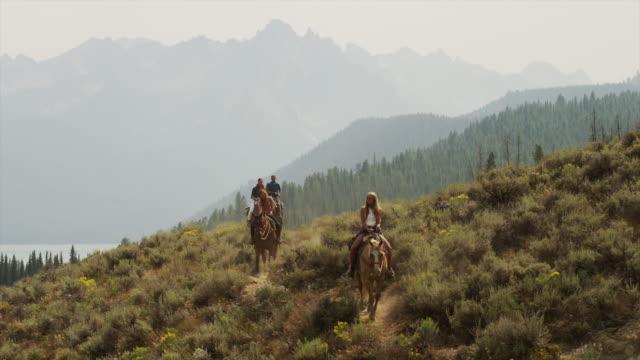 vídeos de stock e filmes b-roll de wide shot of friends horseback riding near lake / idaho, united states - fotografia de três quartos