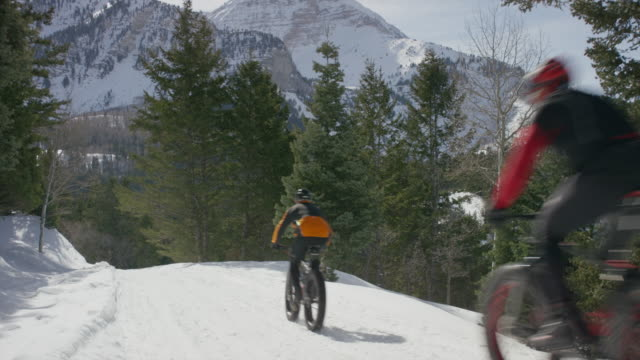 wide shot of friends riding fat bikes on mountain / american fork canyon, utah, united states - american fork canyon bildbanksvideor och videomaterial från bakom kulisserna