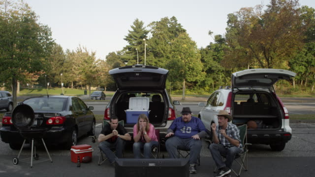 wide shot of friends tailgating and cheering - cool box stock videos & royalty-free footage