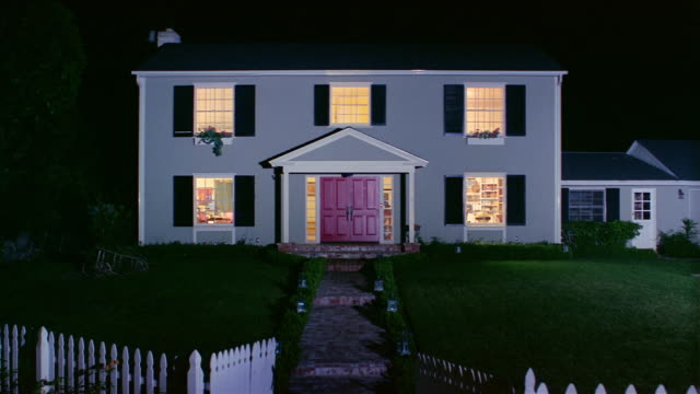 Wide shot of front of suburban house at night / lights turning on inside / lights turning off / Santa Barbara, California