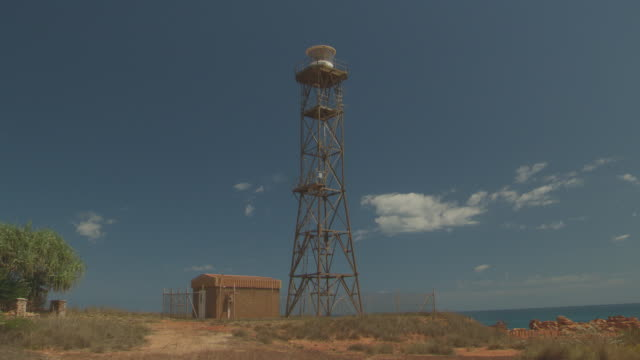 vídeos de stock, filmes e b-roll de wide shot of gantheaume point lighthouse tower / various shots of red coastal sandstone formations alternating with pan of cable beach, indian ocean,... - cable