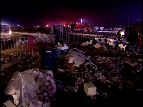 Wide shot of garbage and trucks