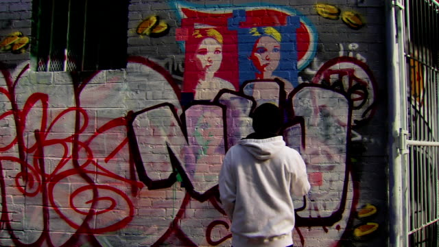 wide shot of graffiti artist painting urban wall - graffiti stock videos & royalty-free footage