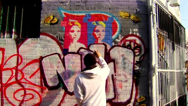 wide shot of graffiti artist painting urban wall - graffiti stock videos and b-roll footage