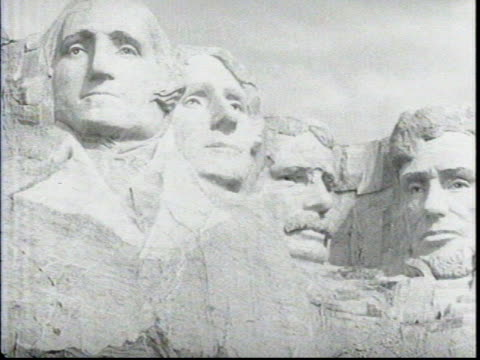 wide shot of gutzon borglum and his workers standing at base of monument looking up at the completed monument / closer view from top of tree line /... - hügelkette stock-videos und b-roll-filmmaterial